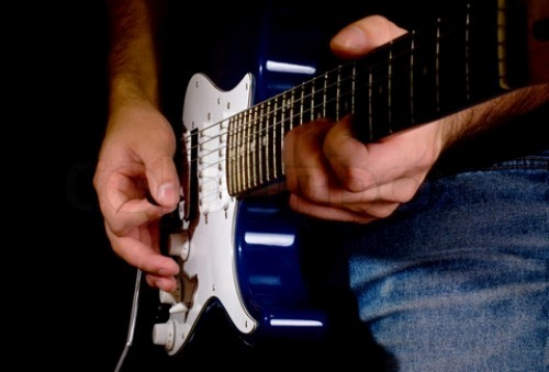 man playing on electric guitar in the dark closeup